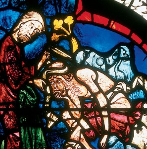 The Samaritan helps the wounded traveler, as depicted in the Chartes window.