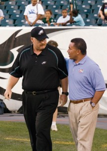 Andy Reid and Vai Sikahema, one-time teammates at BYU, walk across Lincoln Financial Field before the final 2005 preseason game.