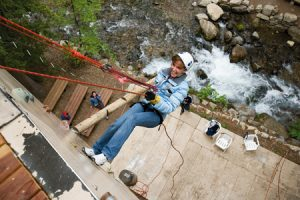 Suspended some 30 feet above the North Fork of the Provo River, a camp participant experiences Aspen Grove's rappelling and climbing wall.