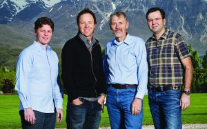 Qualtrics founders Stuart Orgill, Ryan Smith, Scott Smith, and Jared Smith stand next to each other in front of mountains.