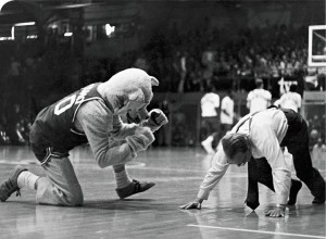 50 years ago: With encouragement from Cosmo, BYU president Ernest L. Wilkinson (BA '21) demonstrates his athletic prowess by performing 47 push-ups at a home basketball game in 1964.