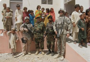 Doug Herrin (far right), local children, and Afghan National Army leaders celebrate the completion of a school in a village just east of Kandahar in August 2008.