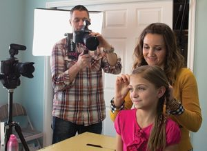 Mindy McKnight does her daughter's hair while dad, Shaun McKnight, films