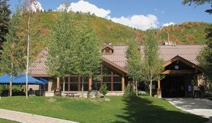 Trees, hills, streams, wildlife, and steep canyon walls surround Aspen Grove's modern lodges and rustic cabins, immersing guests in a mountain environment.