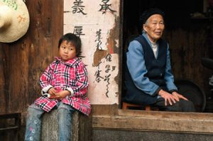 "In order to support their family, many Chinese parents travel to jobs in the cities, leaving their children in the care of grandparents. John Telford observed that ""Children in the more remote villages were, for the most part, seen in Western-style clothes;...the older person was typically dressed in traditional Chinese clothing."" Photo by John Telford."