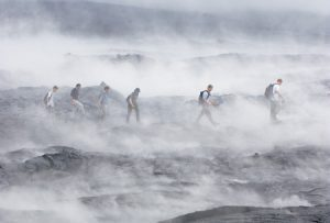 BYU geology students trek through misty lava fields. Steam produced by rain on the fields made it impossible for the group to locate active lava flows during their first day's seach.