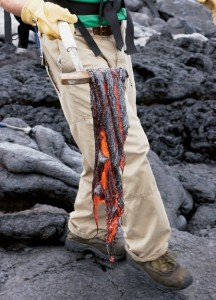 Still-glowing lava retrieved from a nearby flow begins to take on a charcoal-like hue as it cools.