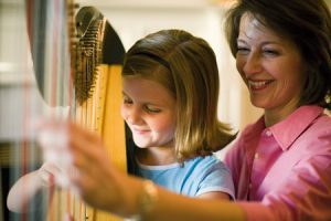 child playing harp with mother