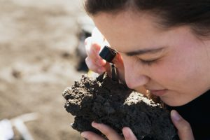 Looking for metal alloys, Nichelle Baxter examines a crusted lava bomb. Alloys in these volcanic chunks may indicate that a large ore deposit is brewing below.