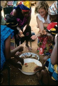 During a break at a literacy meeting in a Mali village, OUA worker Michelle Hagen enjoys a traditional meal with local women. BYU research shows that NGOs are more often successful when workers value the local culture.