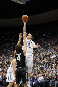 Tyler Haws jumping, about to release the ball while a member of the other team reaches up to block him.