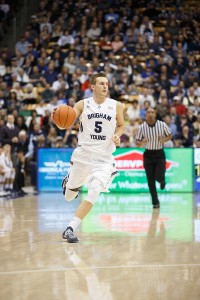 Kyle Collinsworth running down the court with the basketball in his hand.
