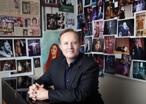Darrell Babidge sitting in his office with pictures of his students performances around him on the walls.