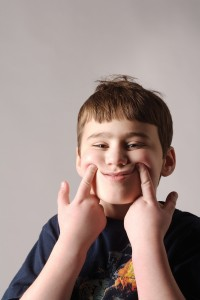 A young boy using his pointer fingers to shape his mouth into a smile.