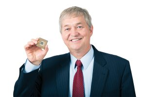 Richard Brown holding a small square container holding a chip he created.