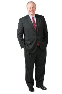 Gregory F. Hebertson, a man standing in a black suit with a button up shirt and a tie.