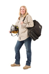 Susan Kochevar is standing to the left holding her fire department hat and a large emergency bag.