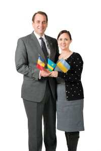 David and Chelom Leavitt standing side by side holding three small foreign flags.