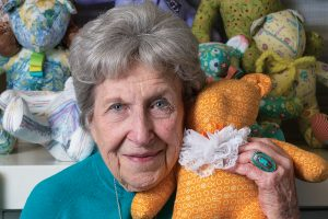 Ruth Brasher holding one of her home made teddy bears. There are other bears in the background.
