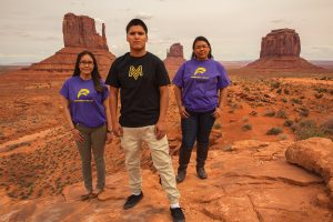 Two girls and a boy sporting their shirts with new logos on red rocks in Southeast Utah.