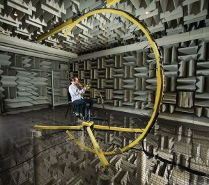 A student sitting in a suspended chair in the anechoic chamber. He is playing the trombone into 37 microphones that are connected to this C-shaped device. Wedges line the chamber.