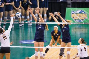 Two BYU women Volleyball players jumping to block the volleyball.