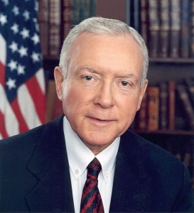 Portrait of Orrin Hatch with the American Flag and a bookcase behind him.