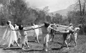 An old photo of BYU students joined in a circle holding hands performing a dance in flowing costumes.