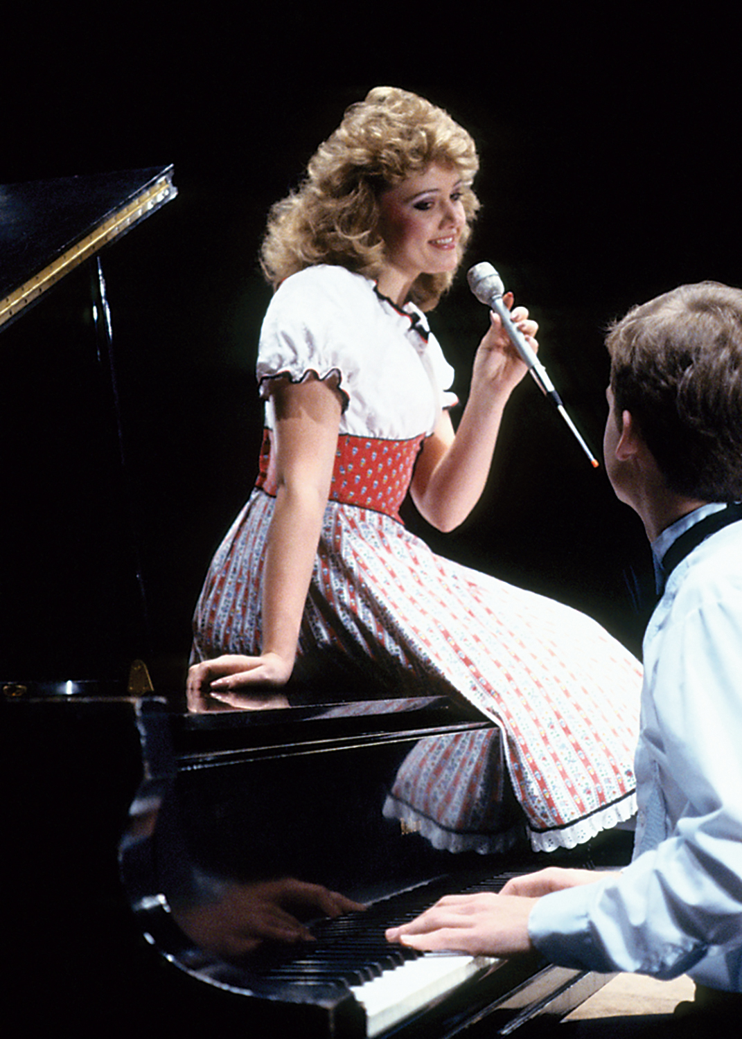 A woman sitting on the piano with a microphone in hand gazing at the man playing the piano.