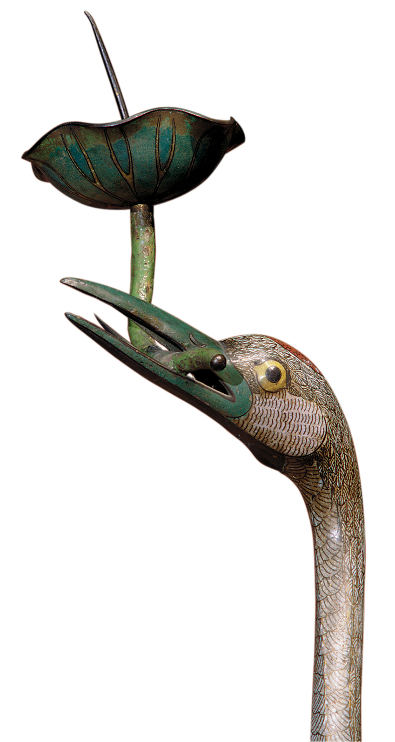 A candleholder in the form of a crane with its beak open and holding a flower.
