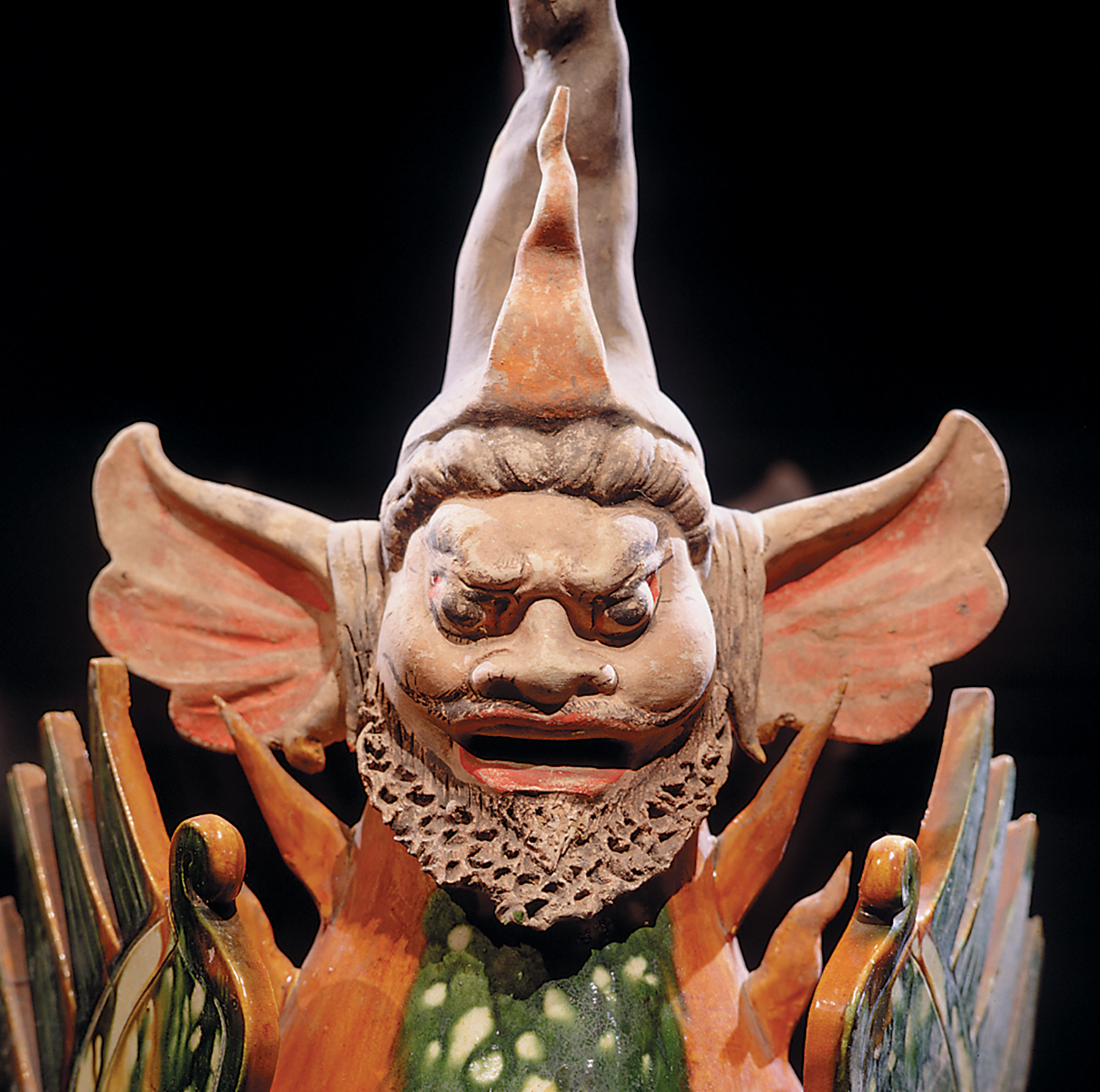 A ceramic figurine of a human face with a dragon body.