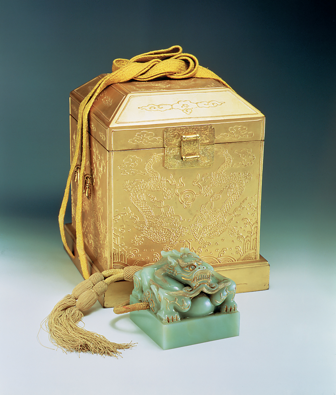 A jade seal with a dragon design and its ornamental case with drawings embossed on it.