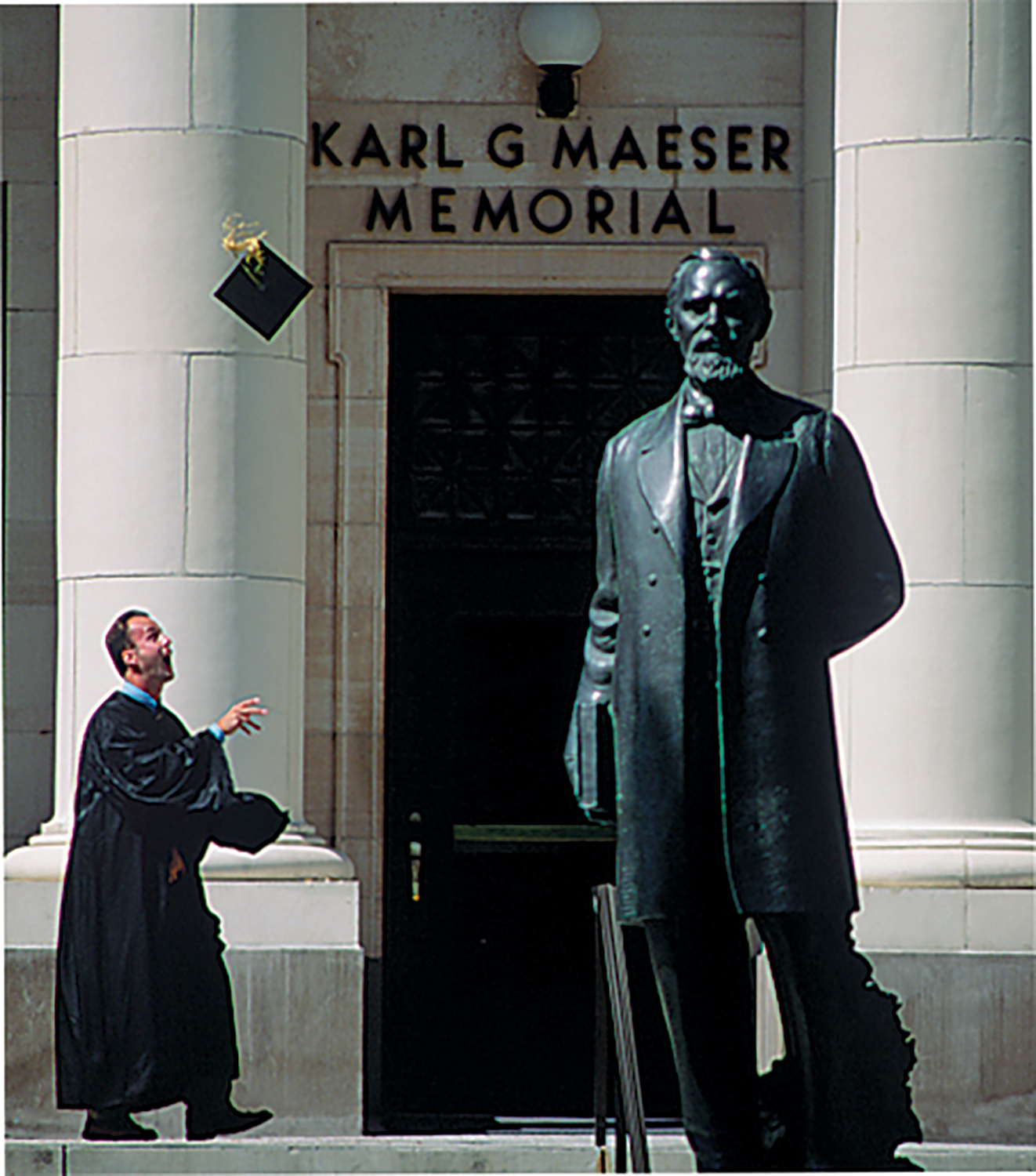 A graduate throwing his hat into the air next to a statue of Karl G. Maeser