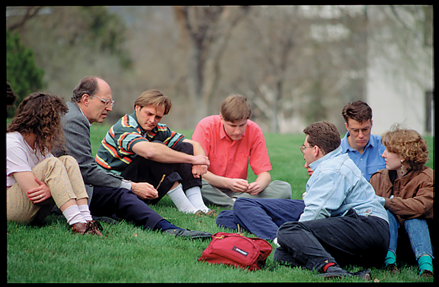 A few students gathered around on the grass surrounding their teacher as he talks to them.