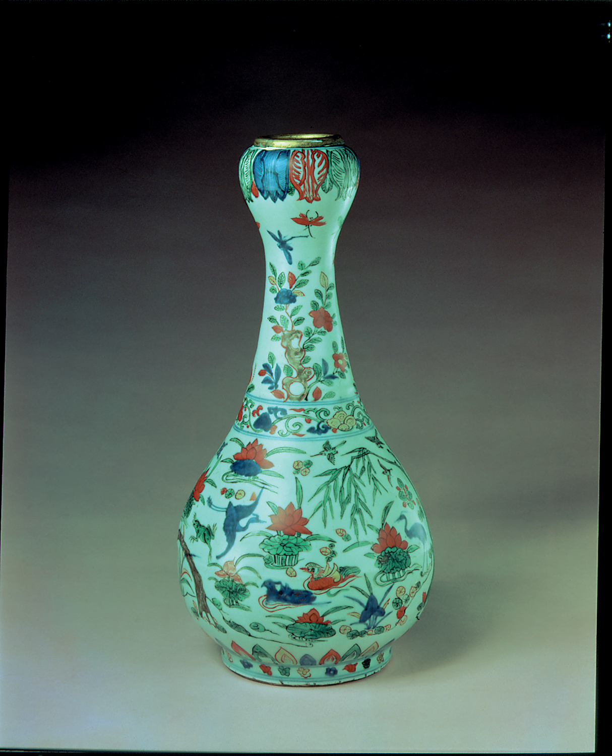 A porcelain vase with a round base and a skinny neck. Colorful flowers and designs are on the vase.