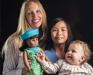 Rebecca Christensen de Schweinitz with her children and the newly released American Girl Doll Melody.