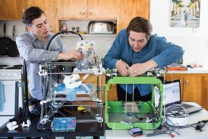 Scott Harris and Ryan Garrison hover over their 3-D printer
