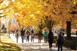 A picture of students walking on campus in the fall.