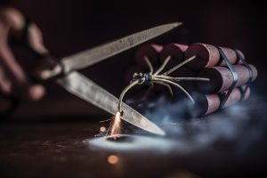 Scissors cut the wick on a stick of dynamite, preventing it from exploding.