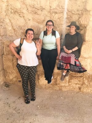 Hannah Lambert and friends stand in front of rock in hiking gear