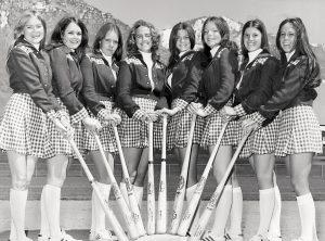 Eight BYU female students hold bats on the campus baseball diamond.
