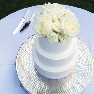 a photo of a white, three-tiered cake that is topped with white roses and displayed on a table with a white tablecloth
