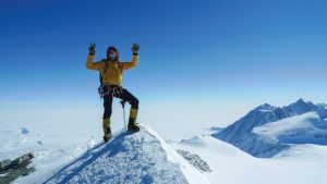 Martin Frey stands on the peak of Antarctica's Mount Vinson with his hands in the air