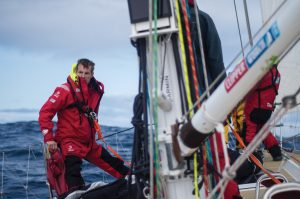 Martin Frey leans on the edge of his race yacht as he crosses the North Pacific ocean.