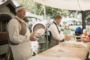 Gove Allen dressed in period costume making bread under a tent