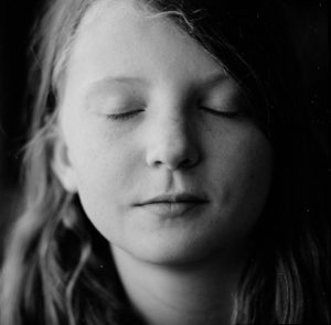 A black-and-white photo of the author's daughter, who is closing her eyes