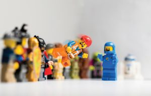 Lego figures stand at attention and watch as one figure flies through the air with a surprised look on its face.