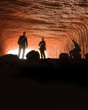 Characters from the new BYUtv show Extinct pose dramatically in a red-rock tunnel.