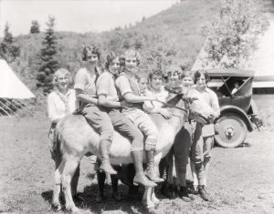 Three female students sit a top a burro at the Alpine Summer School. Photo from BYU Special Collections.