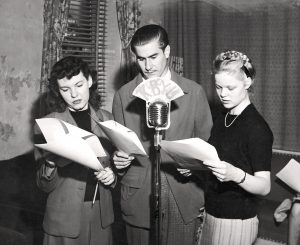 Three students gather around a microphone, performing a dramatic reading in a 1946 radio workshop at BYU. Photo from BYU Special Collections.